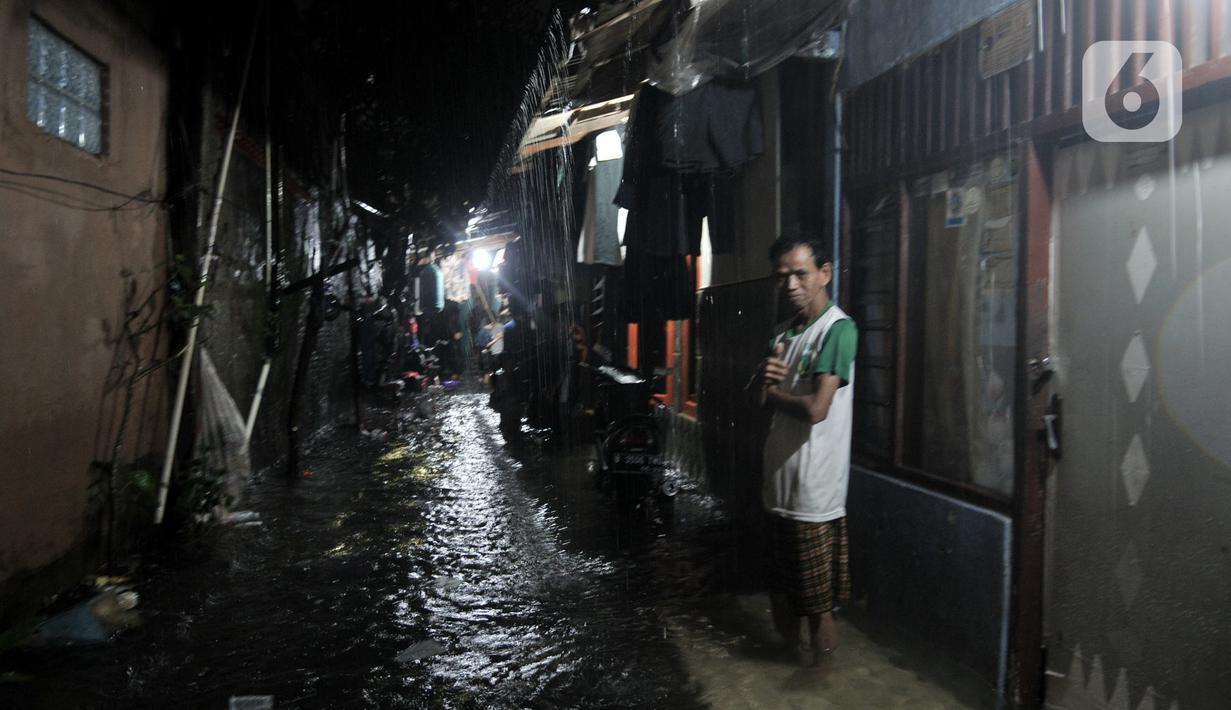 Warga berada di depan rumah saat banjir di kawasan Cipinang, Jakarta Timur, Minggu (23/2/2020) dini hari. Hujan deras yang mengguyur Jakarta dan sekitarnya sejak Sabtu malam ditambah buruknya drainase menyebabkan ratusan rumah di Cipinang terendam banjir. (merdeka.com/Iqbal S. Nugroho)