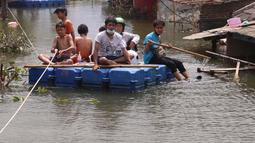 Warga melintas dengan perahu buatan saat banjir melanda perumahan Periuk Damai, Tangerang, Banten, Selasa (22/2/2021). Banjir setinggi 2,5 meter tersebut sudah terjadi selama 4 hari. (Liputan6.com/Angga Yuniar)