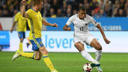Striker Prancis, Kylian Mbappe, berusaha melewati gelandang Swedia, Sebastian Larsson, pada laga kualifikasi Piala Dunia 2018 di Stadion Friends Arena, Solna, Jumat (9/6/2017). Swedia menang 2-1 atas Prancis. (AFP/Franck Fife)