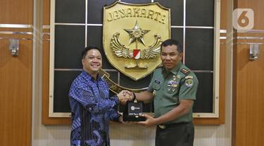 Director Programming SCTV, David Suwarto (kiri) memberikan plakat ke Pangdam Jaya Mayjen TNI Eko Margiyono seusai kunjungan di Makodam Jaya, Jakarta, Selasa (10/12/2019). Kunjungan ini untuk menjalin hubungan kedua pihak. (Liputan6.com/Herman Zakharia)