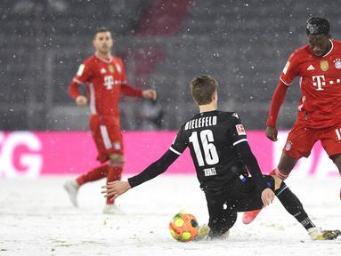 Pemain Bayern Munchen Alphonso Davies (kanan) memperebutkan bola dengan pemain Arminia Bielefeld Fabian Kunze pada pertandingan Bundesliga di Allianz Arena, Munich, Jerman, Senin (15/2/2021). Laga berakhir dengan skor 3-3. (AP Photo/Andreas Schaad, Pool)