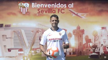 Penyerang baru Sevilla, Javier Hernandez 'Chicharito' berpose dengan jersey klub barunya selama presentasi resminya di Sport City of Sevilla (2/9/2019). Eks penyerang Manchester United dan Real Madrid ini digaet Sevilla dengan mahar yang dikabarkan mencapai 8 juta euro. (AFP Photo/Cristina Quicler)