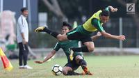 Pemain Indonesia U-19, Aulia Hidayat melompat menghindari tekel saat game internal di Lapangan A Kompleks GBK, Jakarta, Rabu (3/10). Laga internal ini untuk menentukan skuat utama Timnas Indonesia di Piala Asia U-19. (Liputan6.com/Helmi Fithriansyah)