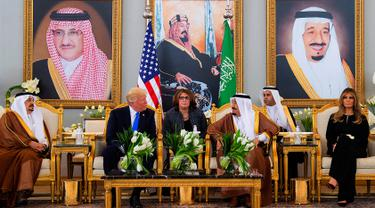 Presiden AS Donald Trump didampingi Melania Trump saat menemui Raja Arab Saudi Salman bin Abdulaziz al-Saud di Riyadh (20/5). Kunjungan ini merupakan kunjungan luar negri Trump pertama sebagai Presiden AS. (AFP/Saudi Royal Palace/Bandar Al-Jalou)