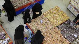 Warga Yaman membeli permen dan kacang-kacangan saat umat Islam bersiap untuk merayakan liburan tahunan Idul Adha (Hari Raya Kurban) di supermarket di ibu kota Sanaa (18/7/2021). (AFP/Mohammed Huwais)