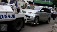 Petugas menderek kendaraan roda empat yang parkir sembarangan di kawasan Tanah Abang, Jakarta, Senin (14/11). Razia dilakukan menyusul maraknya parkir liar di kawasan Tanah Abang yang kerap menimbulkan kemacetan. (Liputan6.com/Gempur M Surya)
