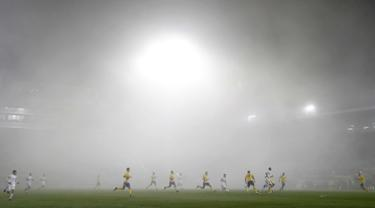 Pemain FC Fastav Zlin dan F.C. Copenhagen saat bertanding dengan suasana kabut tebal pada Grup F Liga Europa di Stadion Andruv, Ceko (19/10). Kabut tebal mendadak menutup stadion yang menyebabkan berkurangnya jarak pandang. (AP Photo/Petr David Josek)