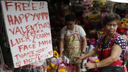 Toko bunga menawarkan pesona keberuntungan dan masker wajah gratis sebagai bagian dari promosi Hari Kasih Sayang di Alabang, Manila, Filipina (13/2/2020). (AP Photo/Aaron Favila)