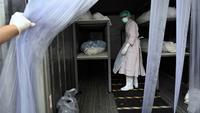 Pekerja bersiap memindahkan jenazah korban Covid-19 dari wadah (kontainer) berpendingin ke dalam peti mati di luar kamar mayat Rumah Sakit Thammasat, utara Bangkok, Rabu (4/8/2021). Thailand mencapai rekor tertinggi yakni lebih dari 20.000 kasus infeksi baru dalam sehari. (Lillian SUWANRUMPHA/AFP)