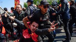 Polisi Turki menangkap seorang pemrotes yang mencoba menentang larangan dan berbaris di Lapangan Taksim saat peringatan Hari Buruh di Istanbul, Turki (1/5). (AFP/Yasin Akgul)