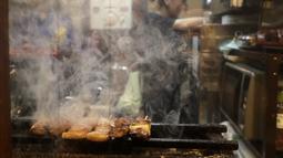 Yakitori saat dibakar di sebuah bar di area jalan malam belakang pusat kota Tokyo (4/10/2019). Yakitori merupakan sate khas dari Jepang yang umumnya menggunakan daging ayam.  (AP Photo/Mark Baker)