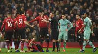 Wasit Andre Mariner menenangkan para pemain Manchester United saat melawan Arsenal pada laga Premier League di Stadion Old Trafford, Manchester, Rabu (5/12). Kedua klub bermain imbang 2-2. (AFP/Oli Scarff)
