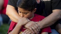Seorang anak memegang tangan ayahnya saat menghadiri acara berjaga-jaga untuk korban penembakan brutal di festival kuliner Gilroy Garlic di Gilroy, California (29/7/2019). Dalam kejadian tersebut polisi berhasil menembak palaku penyerangan. (AP Photo/Noah Berger)