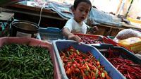 Seorang bocah bermain dengan cabai di sebuah pasar di Jakarta, Kamis (11/1). Jika sebelumnya dijual Rp 30 ribu hingga Rp 35 ribu, kini harga cabai berkisar Rp 55 ribu hingga Rp 60 ribu per kilogram. (Liputan6.com/Angga Yuniar)