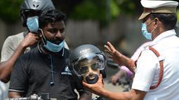 Petugas polisi memegang kepala mockup dengan helm selama kampanye kesadaran keselamatan jalan, di Chennai (7/7/2021). (AFP/Arun Sankar)
