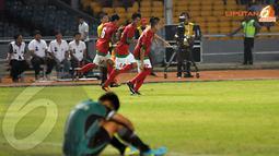 Tiga pemain Timnas Indonesia berlari sambil tersenyum melewati peman Laos yang terduduk lesu usai laskar Merah Putih menambah golnya (Liputan6.com/Helmi Fithriansyah)