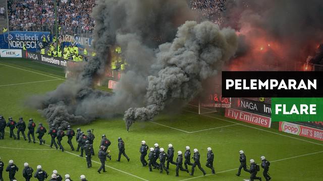 Fans Hamburg tak bisa menerima tim kesayangannya terdegradasi dan coba melemparkan flare ke lapangan.