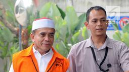 Gubernur Aceh Irwandi Yusuf dikawal petugas berjalan saat tiba di gedung KPK, Jakarta, Rabu (25/7). Irwandi Yusuf diperiksa sebagai tersangka terkait dugaan menerima suap dana Otonomi Khusus (Otsus) Provinsi Aceh tahun 2018. (Merdeka.com/Dwi Narwoko)