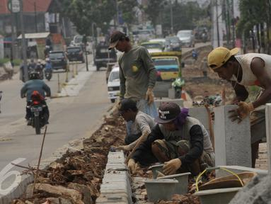 Pekerja saat menyelesaikan proyek rehabilitasi ruas jalan Ciputat-Pamulang, Tangerang Selatan, (28/1). Pemerintah Provinsi Banten akan melakukan rehab pada beberapa titik ruas jalan yang menghabiskan lebih dari Rp 21 miliar. (Liputan6.com/Faisal R Syam)