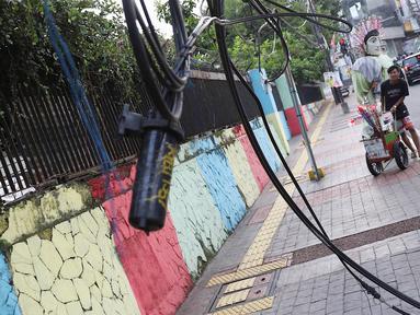 Pejalan kaki melintasi trotoar yang terhalang instalasi kabel di Jalan Kyai Maja, Jakarta, Rabu (10/4). Selain menganggu kenyamanan pejalan kaki, kondisi instalasi kabel yang semrawut tersebut juga berbahaya apabila mengandung aliran listrik. (Liputan6.com/Immanuel Antonius)