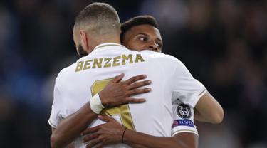 Penyerang Real Madrid, Rodrygo memeluk rekannya Karim Benzema setelah mencetak gol ke gawang Galatasaray pada pertandingan Grup A Liga Champions di stadion Santiago Bernabeu, Spanyol (6/11/2019). Rodrygo mencetak hattrick dipertandingan ini dan mengantar Madrid menang 6-0. (AP Photo/Manu Fernandez)
