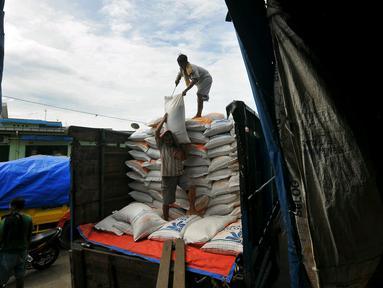 Pekerja menurunkan karung beras di pasar induk Cipinang, Jakarta, Selasa (27/12). Menteri Perdagangan (Mendag) Enggartiasto Lukita mengatakan, stok kebutuhan pokok pangan hingga akhir tahun akan cukup. (Liputan6.com/Angga Yuniar)