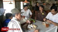 Pemilik restoran fakir miskin gratis, Habib Isyam (kopiah hitam) saat menemani beberapa warga yang sedang menikmati hidangannya di Jalan Ibrahimy, Lingkungan Secang, Kalipuro, Banyuwangi, Jawa Timur. (Foto: Hafil Ahmad/TIMES Indonesia)