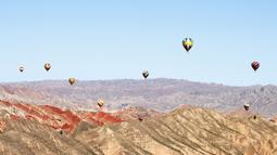 Sejumlah balon udara terlihat di langit Taman Geologi Nasional Danxia di Zhangye, Provinsi Gansu, China barat laut, pada 26 Juli 2020. Sebuah festival balon udara internasional dibuka di Zhangye pada Minggu (26/7). Total 100 balon udara akan ditampilkan dalam festival tersebut. (Xinhua/Cheng Lin)