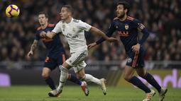 Striker Real Madrid, Lucas Vazquez, beradu cepat dengan gelandang valencia, Daniel Parejo, pada laga La Liga di Stadion Santiago Bernabeu, Madrid, Sabtu (1/12). Madrid menang 2-0 atas Valencia. (AFP/Oscar Del Pozo)