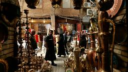 Warga lalu lalang melintasi toko barang antik di Baghdad, Irak, Rabu (20/3). (AP Photo/Hadi Mizan)