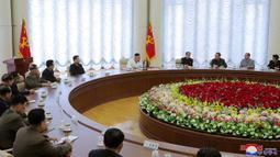 Pemimpin Korea Utara, Kim Jong-un (tengah) menghadiri pertemuan politbiro ke-13 dari Partai Buruh di lokasi yang dirahasiakan dalam gambar yang diambil Minggu (7/6/2020). Dalam pertemuan itu, Kim Jong-un juga membahas proyek-proyek ekonomi termasuk industri kimia. (Photo by STR / KCNA VIA KNS / AFP)
