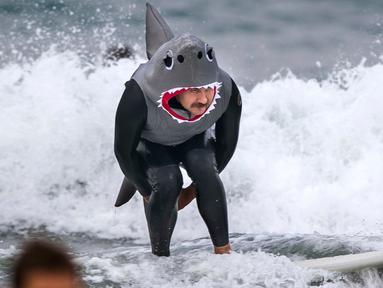 Martin Diaz mengenakan kostum hiu meluncur menaklukkan ombak dengan papan selancar di Newport Beach, California, 28 Oktober 2017. Acara ini untuk merayakan Halloween yang jatuh pada tanggal 31 Oktober. (Paul Rodriguez/The Orange County Register via AP)