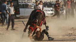 Seorang joki terjatuh saat mengikuti balap kuda di Rafah, Jalur Gaza, Palestina, Selasa (10/9/2019). Balapan kuda tradisional Palestina tersebut digelar di bekas lokasi bandara Jalur Gaza yang telah hancur. (AFP Photo/Said Khatib)