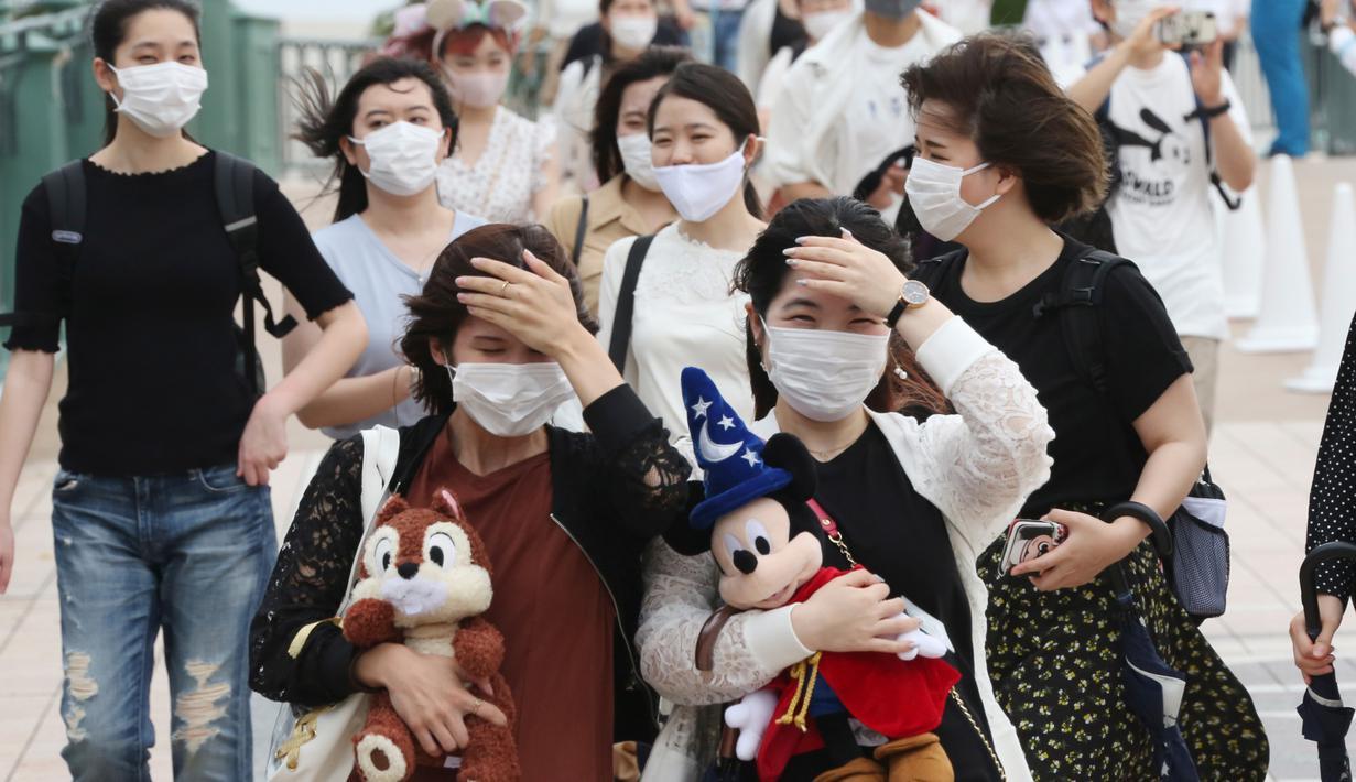 Pengunjung mengenakan masker guna melindungi diri dari virus corona berjalan menuju pintu masuk Tokyo Disneyland di Urayasu, dekat Tokyo, Rabu (1/7/2020). Tokyo Disneyland dibuka kembali untuk pertama kalinya dalam empat bulan setelah menangguhkan operasi karena kekhawatiran Covid-19. (AP/Koji Sasah