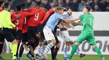 Kiper Rennes Romain Salin (kanan) berkelahi dengan pemain Lazio saat pertandingan Grup E Liga Europa di Stadion Roazhon Park, Rennes, Prancis, Kamis (12/12/2019). Lazio gagal lolos ke 32 besar Liga Europa setelah kalah dari Rennes 2-0. (AP Photo/David Vincent)