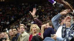 Pemain Los Angeles Lakers, Kobe Bryant melompati deretan penggemar setelah menyelamatkan bola saat bertanding melawan Houston Rockets di Houston pada 20 Desember 2001. Bryant memenangkan lima gelar juara NBA dan peraih medali emas Olimpiade dua kali. (AP Photo/Pat Sullivan)