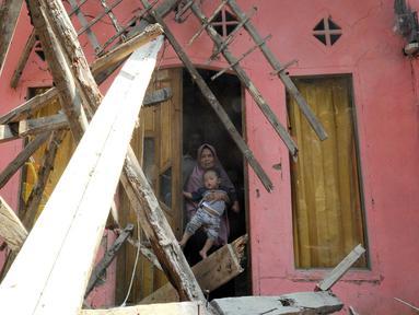 Warga berdiri di pintu rumahnya yang hancur setelah gempa mengguncang Mandalawangi, Pandeglang, Banten, Sabtu (3/8/2019).  Jumlah bangunan rusak akibat gempa berkekuatan 6,9 magnitudo yang mengguncang Banten terus bertambah. (merdeka.com/Arie Basuki)