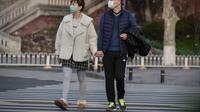 Warga Wuhan, Provinsi Hubei, berjalan-jalan di luar mengenakan masker. (dok. STR / AFP)