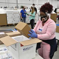 Seorang karyawan di distributor McKesson Corporation mengemas sekotak vaksin Johnson & Johnson ke dalam pendingin untuk dikirim di Shepherdsville, Kentucky, Senin (1/3/2021). Vaksin Covid-19 Johnson & Johnson menjadi vaksin corona ketiga yang sah digunakan di AS. (AP Photo/Timothy D. Easley, Pool)