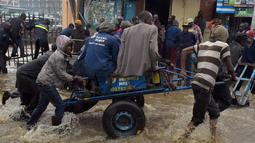 Pejalan kaki menggunakan gerobak melintasi banjir dalam perjalanan ke tempat kerja setelah hujan deras di Nairobi, Kenya (15/3). (AFP Photo/Simon Maina)