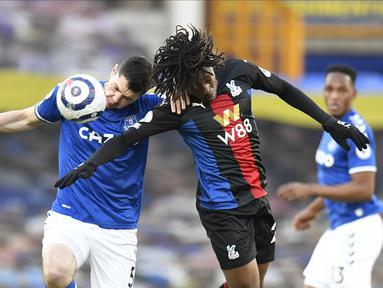 Bek Everton, Michael Keane dan gelandang Crystal Palace, Eberechi Eze bersaing memperebutkan bola pada pekan ke-30 Liga Inggris di Goodison Park, Selasa (6/4) dini hari WIB. Duel Everton vs Crystal Palace harus berakhir imbang dengan skor 1-1. (Peter Powell / Pool via AP)