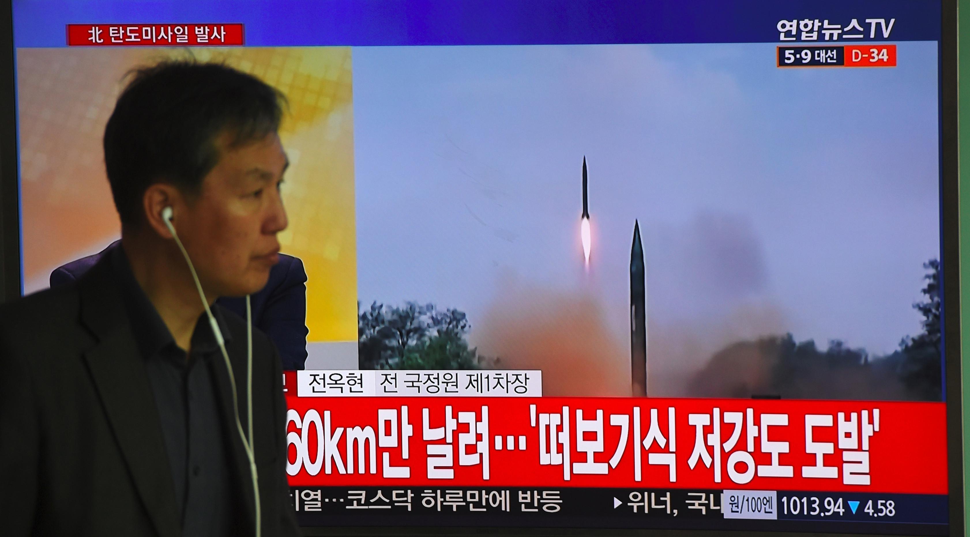 Seorang pria melewati layar televisi yang menyiarkan berita peluncuran rudal oleh Korea Utara (Korut), di sebuah stasiun kereta di Seoul, Korea Selatan, Selasa (5/4). Rudal itu ditembakkan dari wilayah timur Korut ke arah Laut Jepang. (JUNG Yeon-Je/AFP)