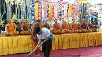 Seorang petugas kebersihan menyapu karpet di hadapan para bhiksu yang bermeditasi di Candi Mendut. (foto: Liputan6.com/danu kisworo/edhie prayitno ige)