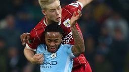 Pemain Manchester City, Raheem Sterling dan pemain Bristol City, Milan Duric berebut bola pada leg pertama semifinal Piala Liga Inggris di Stadion Etihad, Selasa (9/1). Man City menang 2-1 berkat gol telat Sergio Aguero di injury time. (AP/Dave Thompson)
