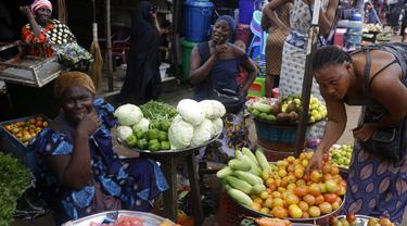Para perempuan menjual sayuran di pasar Kaporo di Conakry, Guinea Senin (13/9/2021). Pasukan elit militer Guinea melakukan kudeta dan menangkap Presiden Alpha Conde pada Minggu, 5 September lalu. (AP Photo/ Sunday Alamba)