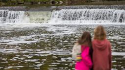 Warga menyaksikan seekor salmon melompati bendungan saat bermigrasi di Sungai Humber di Toronto, Kanada, 18 Oktober 2020. Setiap musim gugur, ribuan ikan salmon di banyak sungai di Ontario berenang menuju ke hulu untuk bertelur, menarik perhatian warga juga para pemancing. (Xinhua/Zou Zheng)
