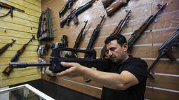 Seorang penjual, Abu Hauraa memeriksa senapan VHS buatan Kroasia di toko senjata berlisensi miliknya di Baghdad, Irak, 24 September 2018. Setelah pelegalan senjata api untuk orang sipil, permintaan akan senjata api semakin meningkat. (AFP/AHMAD AL-RUBAYE)