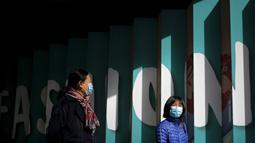 Wanita yang memakai masker untuk mencegah virus corona berjalan melalui pusat perbelanjaan populer ibu kota di Beijing, Selasa (3/11/2020). Sementara virus Corona masih melonjak di seluruh dunia dengan jumlah kematian yang terus meningkat.  (AP Photo/Andy Wong)