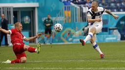 Gelandang Finlandia, Joni Kauko menembak bola saat bertanding melawan Rusia pada pertandingan grup B Euro 2020 di stadion Gazprom Arena di St. Petersburg, Rusia, Rabu (16/6/2021). Rusia Kini mereka sudah mengumpulkan tiga poin dari dua laga, sama dengan Finlandia. (Evgenia Novozhenina/Pool via AP)