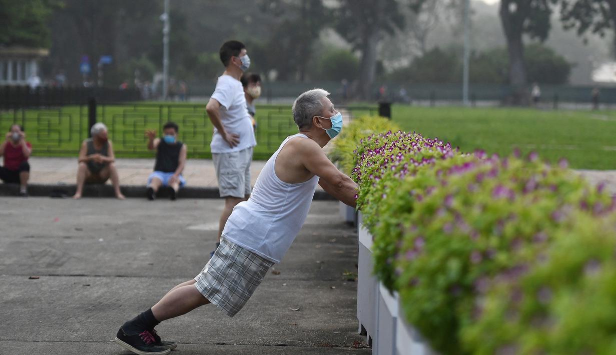 Seorang pria berolahraga di taman umum di Hanoi setelah kegiatan olahraga outdoor diizinkan menyusul pelonggaran pembatasan Covid-19, Selasa (28/9/2021). Sejauh ini, 94 persen dari populasi orang dewasa Hanoi yang berjumlah 5,75 juta telah menerima satu suntikan vaksin COVID-19. (Nhac NGUYEN/AFP)